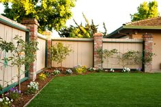 A border of small trees and beautiful flowers lines this well-maintained backyard. A beige fence with green trim and brick columns surrounds the space, providing privacy.