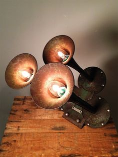 "Rusty Remakes Signature ""Textas Trailer"". Vintage American triple car horn, transformed into a wall lamp or table lamp, depending on preference. A rusty, bent iron plate has been added to the base of the horn to make this angle possible."