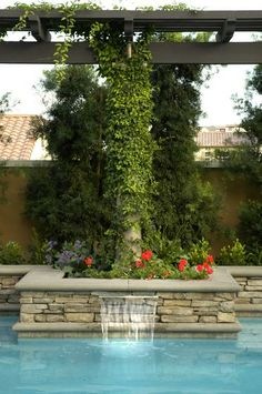 poolside vine-covered pillar above stone wall with water pouring into pool