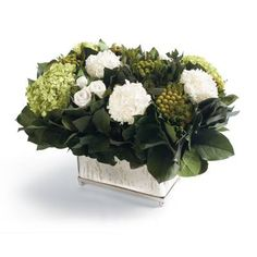 Our breathtaking Innocence Floral Arrangement overflows with an array of pure white banksia, brunia, and hydrangea blossoms set among leafy greenery. They're arranged in an exquisite antique glass mirrored cachepot. Naturally preserved blooms and leaves Hand arranged Round antique glass mirrored cachepot Never needs watering Made in USA