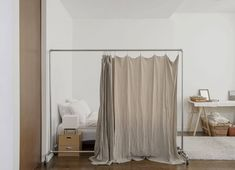 An inventive solution in a shopkeeper's NYC apartment: A DIY room divider—courtesy of a rolling rack fromTed Steel Industries, a pretty linen sheet, and shower curtain rings—separates a sleeping nook from the main living space. SeeShop Owner Makié Yahagi's Charm-Filled Loft in SoHo, New Yorkfor more. Photograph by Matthew Williams and styling by Alexa Hotz for Remodelista.