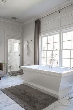 White and gray bathroom features gray walls accented with gray trim moldings lined with a freestanding rectangular tub and a vintage style tub filler placed in front of windows dressed in gray curtains alongside a marble tiled floor laid out in a diamond pattern.