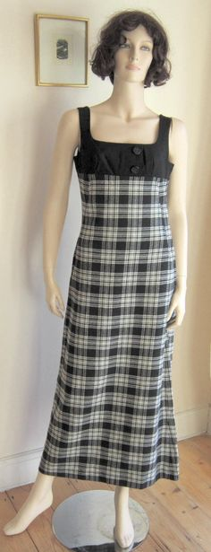 """Dollyrockers, 1960s. """"Maxi pinafore dress. Empire waist-line. Light-medium weight wool fabric. Black and white plaid skirt is unlined. Bodice is lined and features two non-functional decorative buttons with fine fluted design. Dress fastens with side zip and a small metal hook-and-eye closure."""" Priced at $74.99 USD at Etsy shop: Vintage Artizania"""