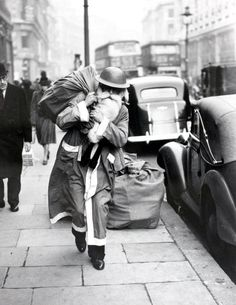 World War Two: 23rd December 1940, Father Christmas walks the streets of wartime London, The old man has exchanged his civilian red hood for a warlike 'tin hat', but, blitz or no blitz, he is delivering goods this year (Photo by Popperfoto/Getty Images)