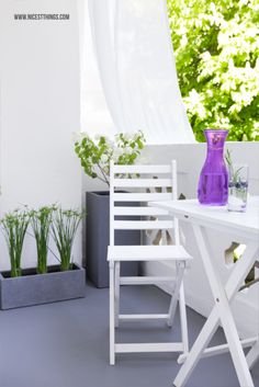 Kleiner Balkon mit schlichter Deko in Grau und Weiss