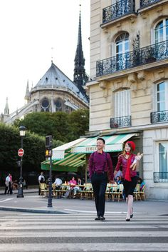 Happy couple crossing the street in Paris holding baguettes in their hands. Picture taken by Fran Boloni during a Paris photo session