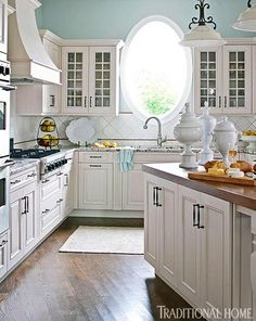 This kitchen's round window floods the space with light - Traditional Home® / Photo: John Bessler / Design: Mary O'Brien Cabaron