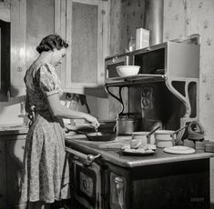 """February 1943. """"Moreno Valley, New Mexico. William Heck ranch. Mrs. Heck getting supper."""" Photo by John Collier, Office of War Information."""