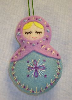Patterned after a Russian nesting doll, this ornament is made with rayon/wool blend felt in baby blue and pink violet, lightly stuffed with