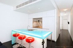 #Kitchen Idea of the Day: Modern white kitchen with backlit blue glass countertop.