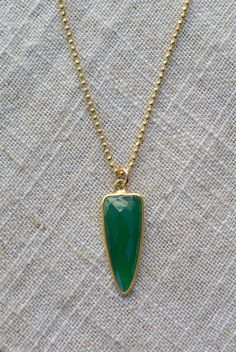 A vibrant green onyx faceted stone hangs freely on a diamond cut ball chain adding a touch of sparkle. The elegant bezel setting allows light to shine