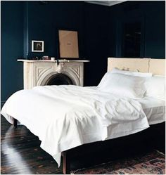 J. Lyons bedroom, featured in Domino Magazine. Dark walls, light bedding, light fireplace