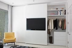 Simple closet system with contemporary, white drawers and floating shelving. Cool flat screen tv built into closet wall and sunny, yellow vintage accent chair.