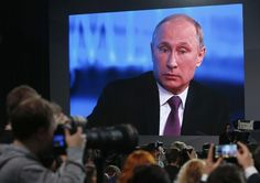 Russian President Putin is seen on a screen during his annual end-of-year news conference in Moscow