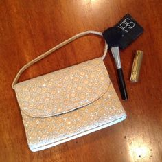 """3 FOR $25  Sparkly lace purse Sparkly silver evening bag with a beige/gold lace overlay. Handle or optional cord shoulder strap. Black lined inside. One small side zipper compartment. Hidden magnetic snap closure under flap. Purse measures 8"""" L x 6"""" H x 2"""" W EUC Bags"""