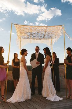 Our satin, laser cut, handheld Arched Chrysanthemum chuppah with gold poles, for a Manhattan rooftop wedding
