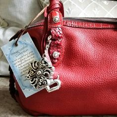 Brighten red leather handbag New, Stylish Brighten red super soft leather handbag with braided handles, and 2 silver hanging embellishments. Brighton Bags