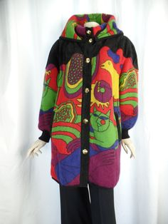 This RARE and UNIQUE wool sweater knit padded jacket is a wonderful example of 60s -70s pop art in bold primary colors, psychedelic style POP ART and beautiful attention to quality and detail- the cartoon-y images of bird, cat and person remind us of Peter Max or Pucci.   Made in Spain by Torras- it features supple black suede leather shoulders with undulating curved edges, front placket and welted pocket trim- suede outside, smooth leather inside. The original 7 pointed cone gold buttons…