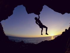 Silhouette of a Man Hanging from a Rock Photographic Print