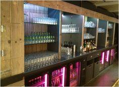 Bar achterwand van steigerhout met gekleurde verlichting.