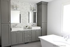 Double vanity with storage towers painted Chelsea Gray, free standing tub, marble mosaic tile backsplash and Formica marble laminate countertop by Kylie M Interiors E-Design