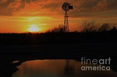 A Windmill Sunset silhouette with a water reflection that's bright and colorful shot in Kansas.