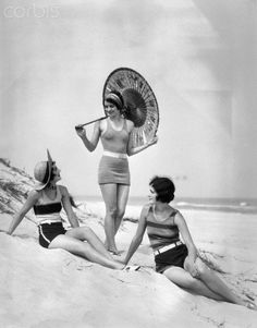 1920s three smiling women in swimsuits at the beach two sitting one standing holding an oriental paper umbrella