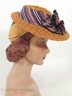 From the late 1930s or early 1940s, a small boater hat. Scalloped natural golden-brown leghorn straw. Asymmetrical brim (wider at front). Richly colored striped fabric around crown forms a jaunty doub