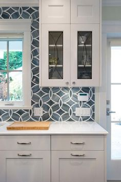 White and blue kitchen boasts white shaker cabinets painted Benjamin Moore White Heron paired with Princess White Quartzite countertops and  an Ann Sacks Beau Monde Glass Polly Tiles in Absolute White and Pearl.