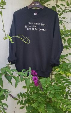 A beautiful and comfortable sweatshirt with a hand stitched quote which says: You were born to be real, not to be perfect. Very unique, just like the