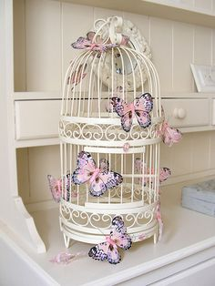 shabby chic white birdcage adorned with pink and purple butterflies