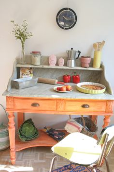 I love the association of this old marble table in orange patina with the yellow chair in formica!