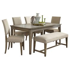 Lend a touch of understated elegance to your mealtimes with this stylish dining set, showcasing a weathered gray finish and nailhead trim details.