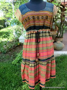 Alicia - Hmong Dress   Colorful woven cotton with Batik, embroidery and flattering drawstring empire waist .  A great mixture of rich colors, pumpkin, wheat, goldenrod , watermelon pink, indigo blue with touches of black.