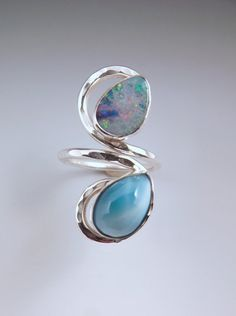 The combination of these stones always reminds me of me to tropical waters. The Opal (11mm x 8mm) has gorgeous sparkling colors like the sun reflecting off the water. This Opal is very colorful with a great area of deep azure blue that matches the Larimar. Paired with the soothing color of the Larimar (12mm x 8mm) only found in the Caribbean- from Etsy Shop LarimarAndSilver. Both stones are bezel set in fine silver to a hammered silver swirl band.