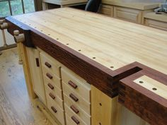 The workbench includes 20 drawers and a storage cabinet which are accessed from both sides.