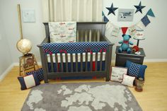 Navy and Red Vintage Airplane crib bedding set in a transportation theme nursery with a globe and airplane art.  Pine Creek Bedding, Judith Raye Art, Lorena Canals washable rug