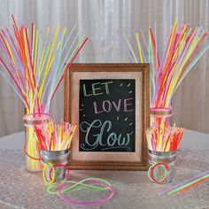 """Let Love Glow Wedding Idea Searching for DIY wedding ideas? Use this glowing idea at your wedding reception for a unique way to draw attention to your guest book, gift table and more. Your guests can grab some glow accessories to light up your reception dance floor!   1. On a piece of chalkboard paper or a chalkboard sign, use chalk or chalk markers to write, """"Let Love Glow!""""  2. Arrange your assortment of glow items in galvanized buckets or a glass jar - whatever matches your reception."""