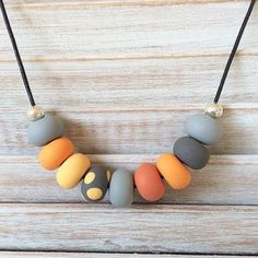 Make a statement with this handmade shades of orange and grey bead necklace. Each polymer clay bead has been individually hand rolled, giving them character. All strung on 27in long genuine leather with a clasp at the back. Every necklace is made with love and care. At Ruby Blue