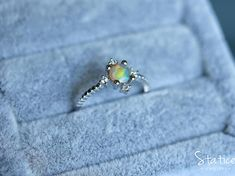 This dainty opal ring features a natural Ethiopian opal set in sterling silver, embellished with cubiz zirconia. The opal stone exhibits a light brown body tone with strong purple, light blue and green shimmers flashing through the stone as you move. The magical iridescence varies