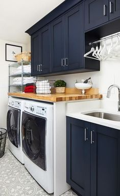 Blue laundry room cabinets featuring a butcher block countertop and closing a white front load washer.