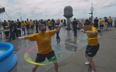 Electrician's Mate Fireman Alexis Hardwick, left, and Electrician's Mate Fireman Sydney Blom hula hoop on the main deck of the U.S. 7th Fleet flagship USS Blue Ridge (LCC 19) during a steel beach picnic in the South China Sea.