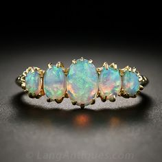 A classic five-stone 'carved' ring from Great Britain, crafted in 18K yellow gold, aglow with a colorful quintet of opals with predominantly green, blue and orange flashes.
