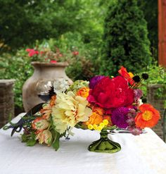 Bright oranges, purples, greens, and yellows are reminiscent of the root vegetables of autumn and their beautiful colors. Peonies, ranunculus, zinnia, scabiosa, feverfew, and Jerusalem sage each bring their own personality to the arrangement. [Fall 2010, Department: Design School, Floral Design: Amy Osaba, Photography: Alecia Lauren Kowalik]
