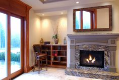 Larger square mirror with crafted wood frame over luxurious and modern fireplace a corner bookshelves with a reading chair