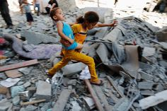 A Palestinian girl carries a child across rubble from a building that police said was destroyed by an Israeli air strike, in the Burij refugee camp in the central Gaza Strip August 1, 2014.
