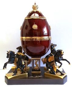 """FABERGÉ egg__Theo Faberge The Horse Tamers""""1849 50 Bridge inspired Fabergé create his """"ANICHKOV EGG Crafted in ornamentally turned sterlin silver overlay cherry red guilloché enamel & accented with pure gold Shell supported 4 horse sculptures bronze Finial vermeil Imperial Crown set cabochon ruby. Surprise within sterling silver pure gold merhorse holding trident Base surprise fully hallmarked W T.Fabergé personal mark as well as his engraved signature. Lim- edit 75 H approxi 8 ¾ i..."""