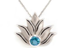 "Lotus Pendant – Petite – Sterling Silver  This pendant is sterling silver with a blue topaz stone. It measures approximately 1/2″ x 1/2″ and comes with an adjustable 16- 22"" coordinating cable chain.  Available now from #AndreaLoprestiFIneJewelry"