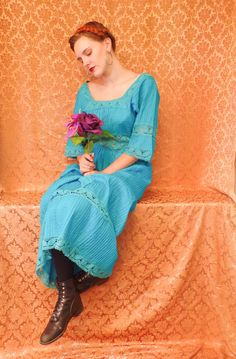 Be the fashionable hippie in this 60s azure blue peasant style maxi dress with see-through lace waist band and mid-length bell sleeves. Vertically woven pleats with a stunning Florentine neckline and empire waist. Zips up in the back. Measurements Bust-40 Empire Waist-30 Length-18 Shoulder to Shoulder-18 Sleeve-13   There is no Label on this garment   Models Measurements Bust-35 Waist-28 Hip- 35.5 Shoulder to Shoulder- 17 Arm Length- 22.5 Height- 56   Follow us on Instagram…