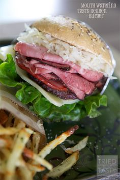 Mouth Watering Tasty Reuben Burger // The name says it all, this mouth watering burger is packed full of flavor and perfect for any BBQ or picnic! Layered high with pastrami and sauerkraut, it's a hearty burger not for the faint of heart! | Tried and Tasty